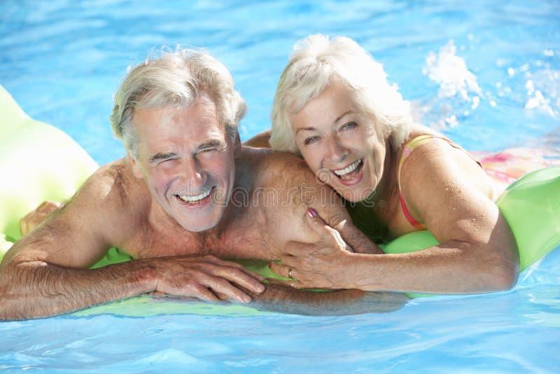 Höga par på ferie i simbassäng royaltyfri fotografi