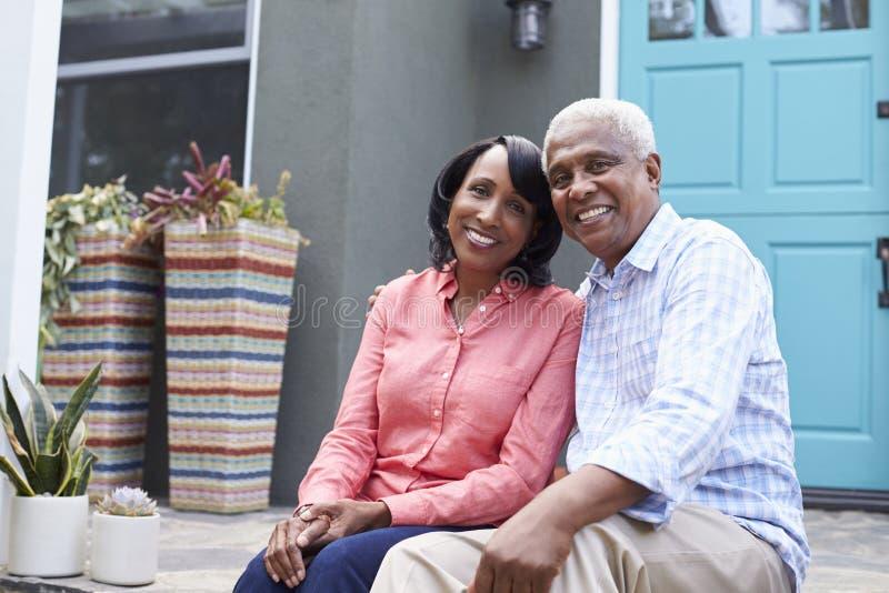 Höga par sitter på moment utanför deras hus, slut upp royaltyfri fotografi
