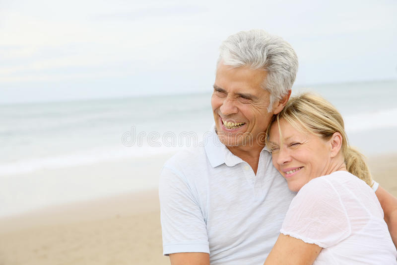 Höga par som är förälskade på omfamna för strand royaltyfria foton
