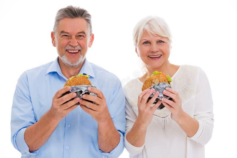Höga par som äter hamburgare royaltyfria bilder