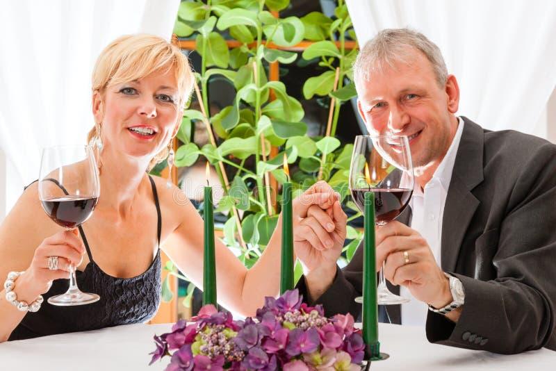 Höga par som äter matställen i restaurang royaltyfri foto