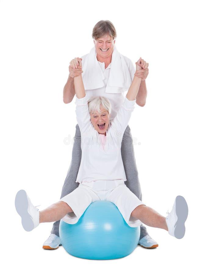 Höga par som övar med pilatesbollen arkivbilder