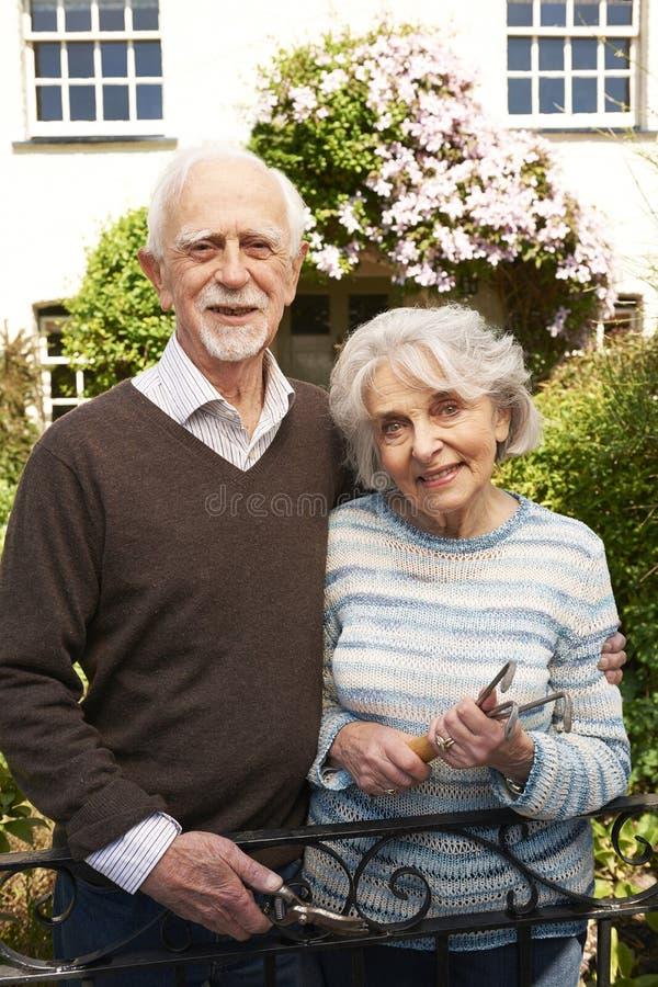 Höga par som arbetar i stugaträdgård arkivfoton