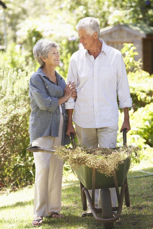 Höga par som arbetar i trädgårds- hemmastatt arkivfoto