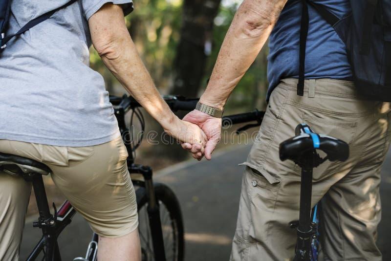 Höga par som cyklar på parkera royaltyfria foton