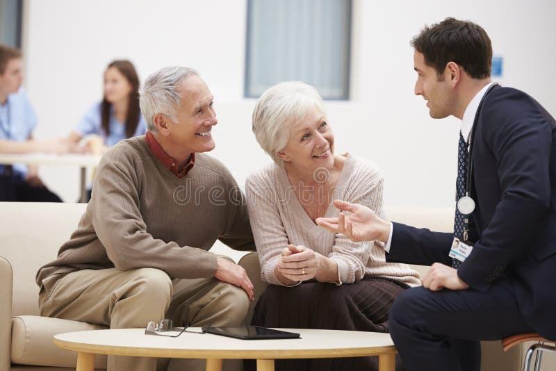 Höga par som diskuterar provresultat med doktorn arkivfoton