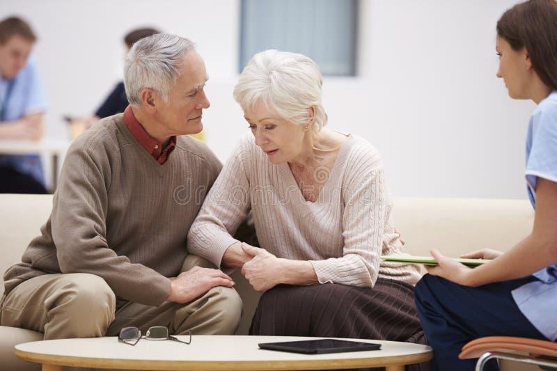 Höga par som diskuterar provresultat med sjuksköterskan royaltyfri fotografi