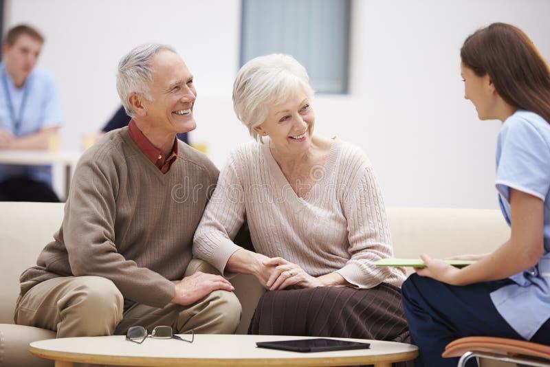 Höga par som diskuterar provresultat med sjuksköterskan royaltyfri bild