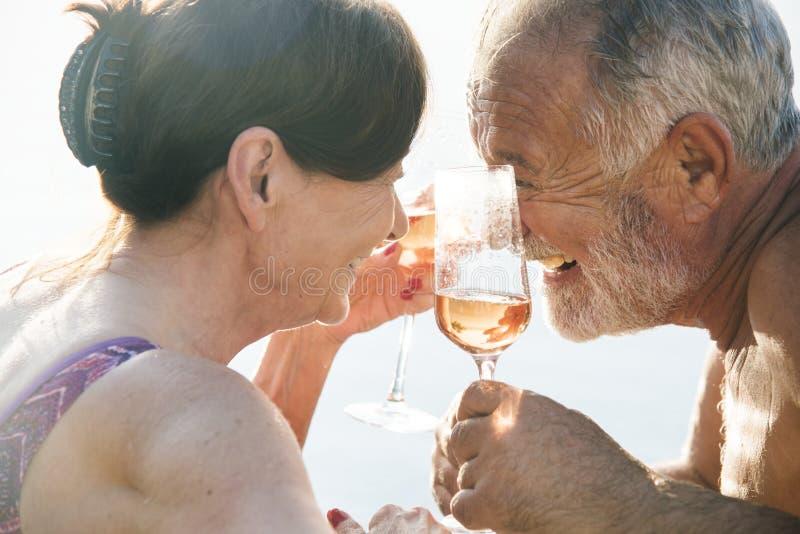 Höga par som dricker prosecco i en simbassäng royaltyfri bild