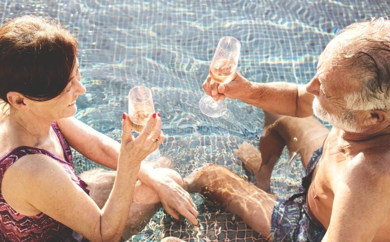 Höga par som dricker prosecco i en simbassäng arkivfoto