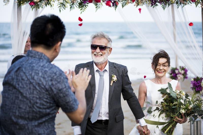 Höga par som får att gifta sig på stranden royaltyfria bilder