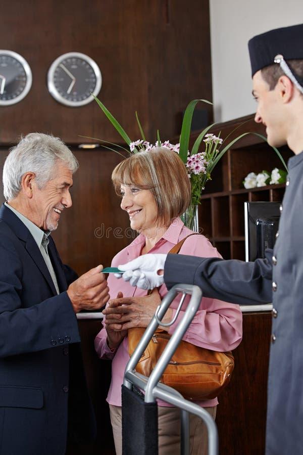 Höga par som får det nyckel- kortet i hotell royaltyfria foton