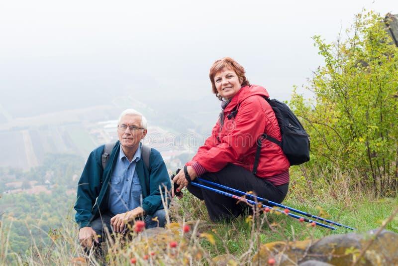 Höga par som fotvandrar och vilar i natur arkivfoton