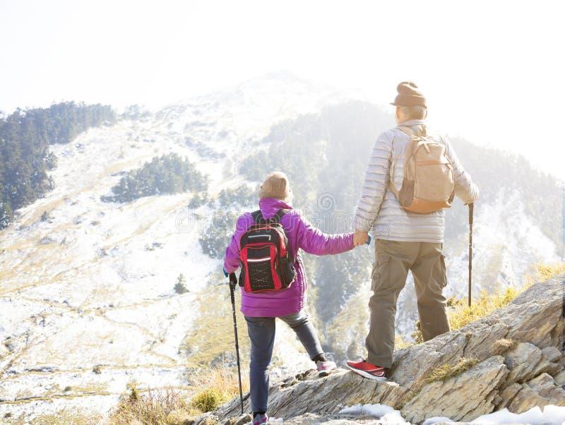 höga par som fotvandrar på berget royaltyfri foto