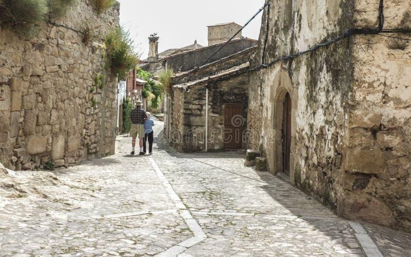 Höga par som går i en medeltida gata i Trujillo, Spanien arkivbild