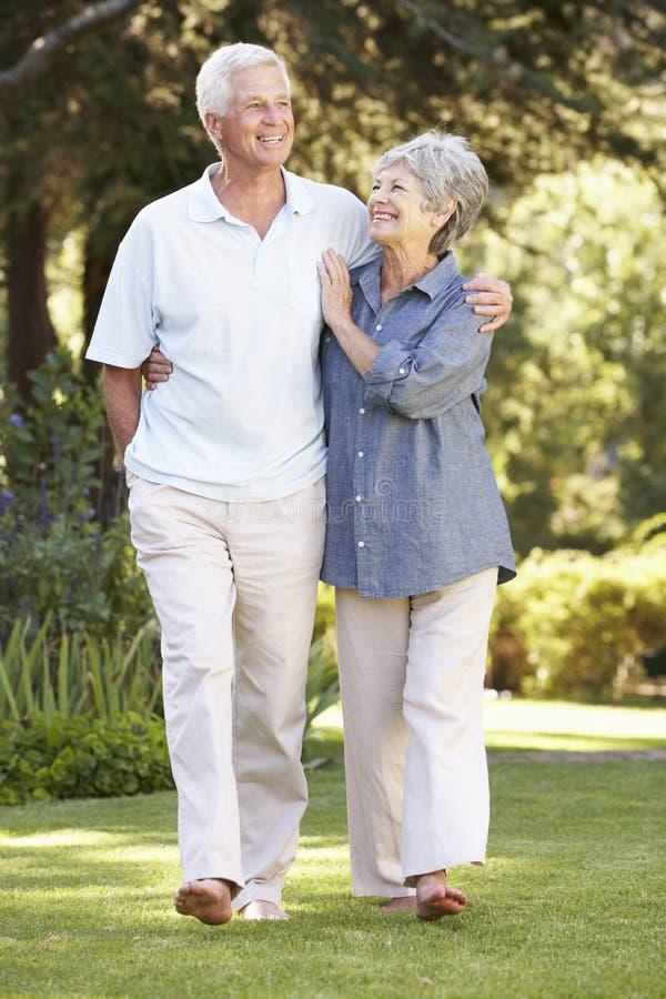 Höga par som går i trädgårds- hemmastatt royaltyfri fotografi