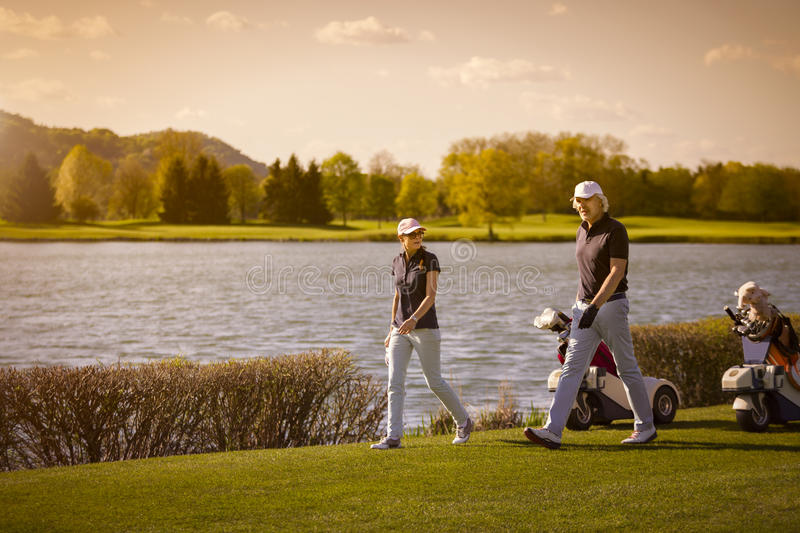 Höga par som går på golfbana royaltyfria bilder