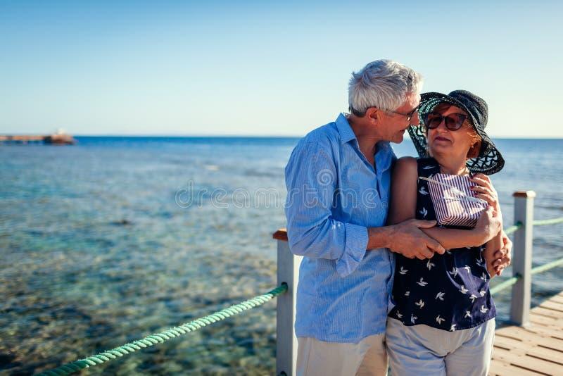 Höga par som går på pir av havet som framlägger gåvor för valentin dag Folk som tycker om semester royaltyfria foton