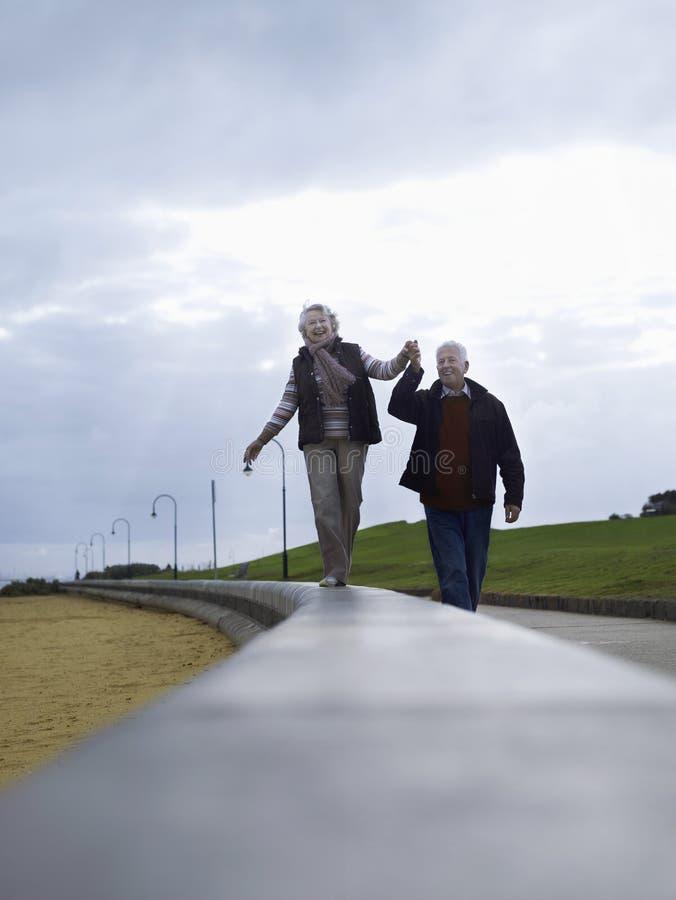 Höga par som går på vägginnehavhänder arkivbilder