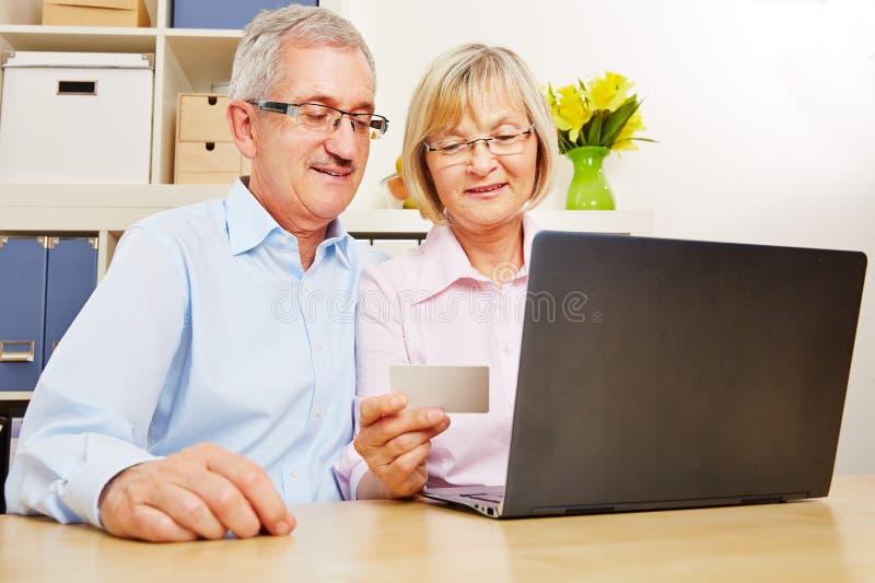 Höga par som gör online-bankrörelsen på datoren arkivfoton