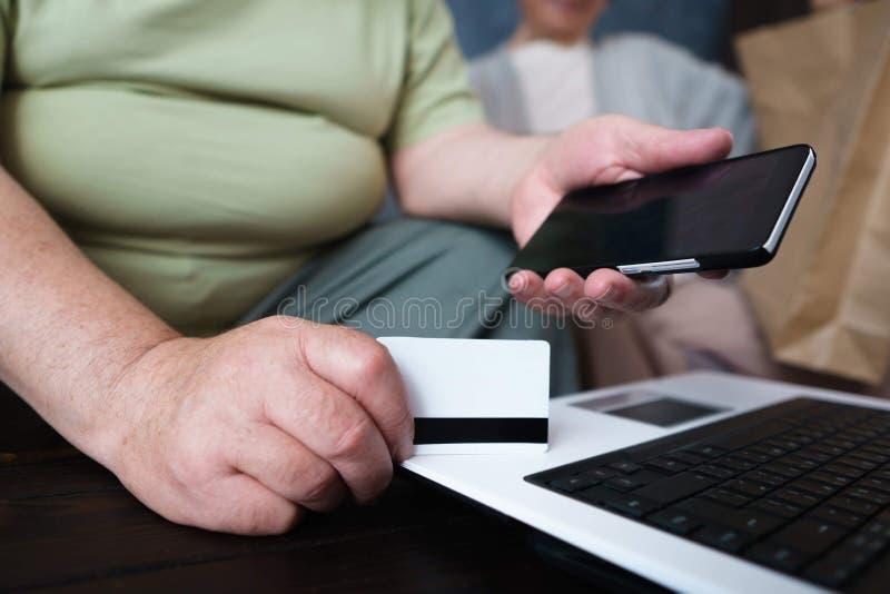 Höga par som gör online-shopping genom att använda grejer royaltyfria foton