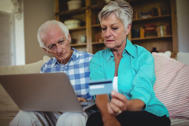 Höga par som gör online-shopping på bärbara datorn arkivfoto