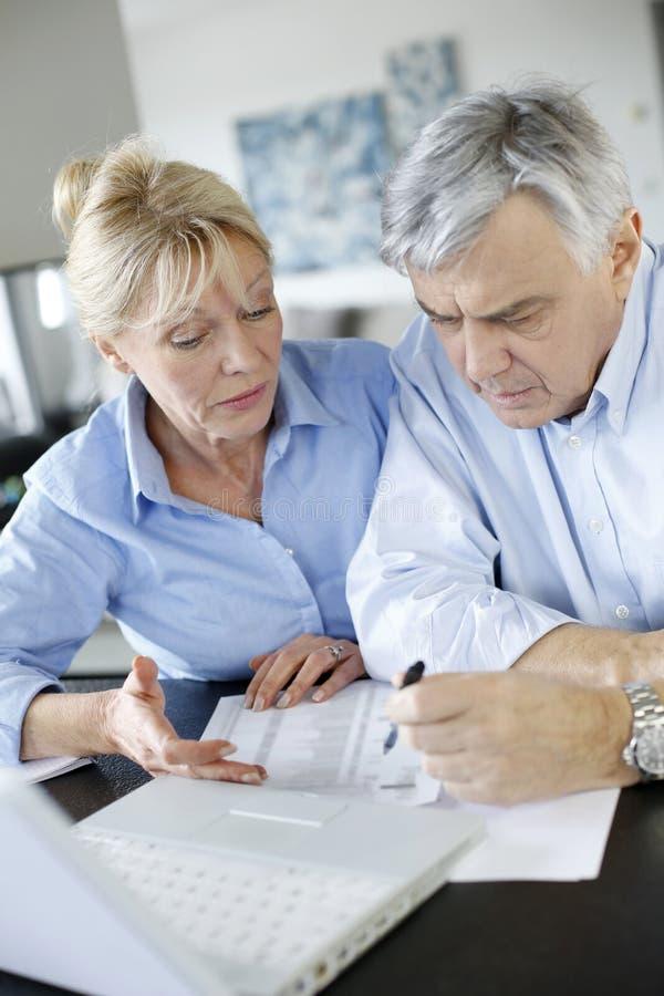 Höga par som gör skrivbordsarbete med internet royaltyfria foton