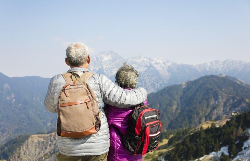 höga par som håller ögonen på bergen royaltyfri bild