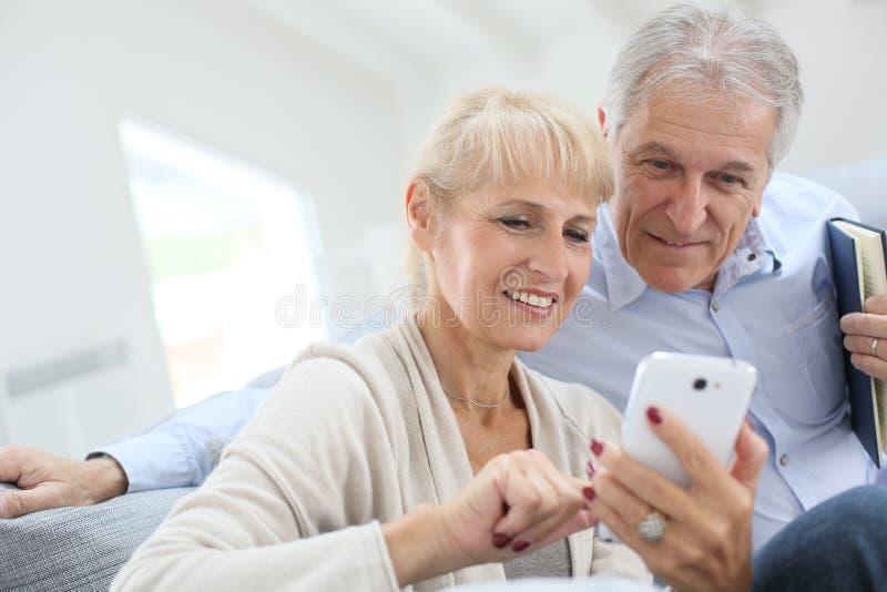 Höga par som har den roliga användande smartphonen royaltyfri bild