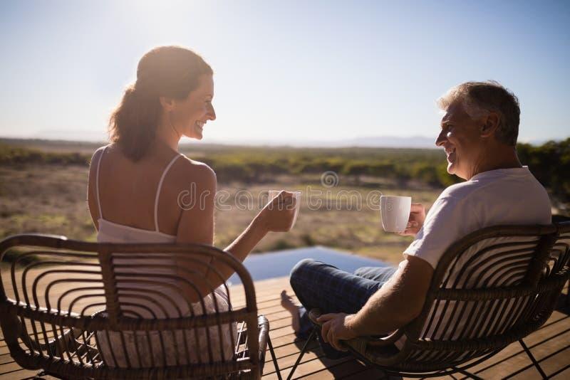 Höga par som har kaffe, medan sitta arkivbilder