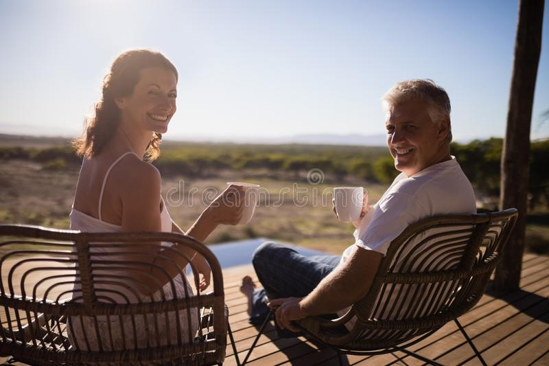 Höga par som har kaffe, medan sitta på semesterorten arkivfoto