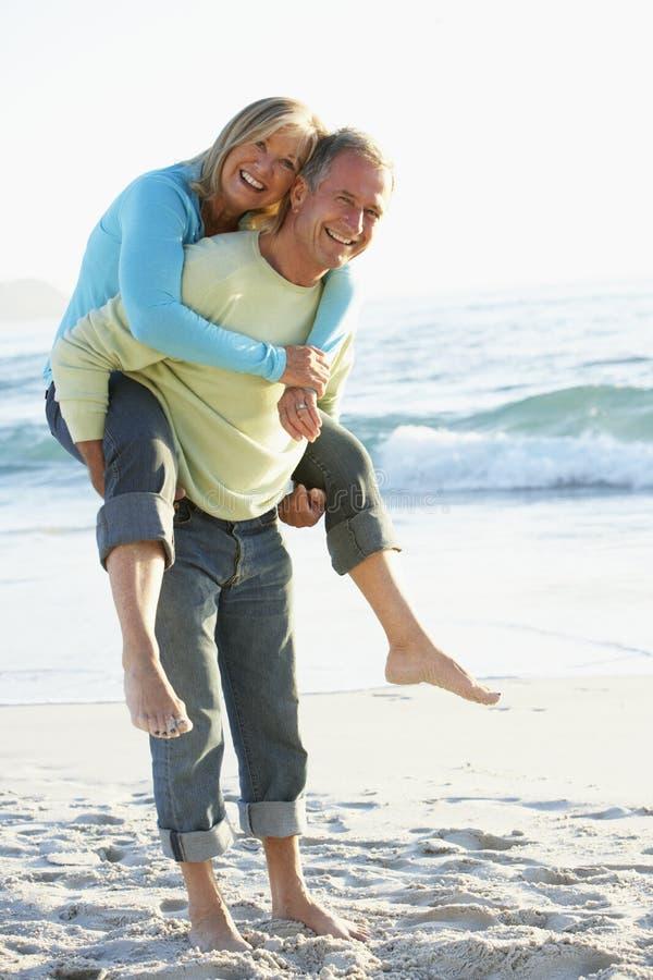 Höga par som har Piggy Bck på Sandy Beach arkivfoto