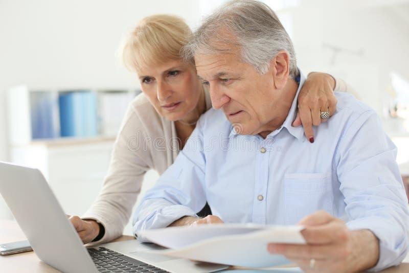 Höga par som hemma gör skrivbordsarbete arkivfoton