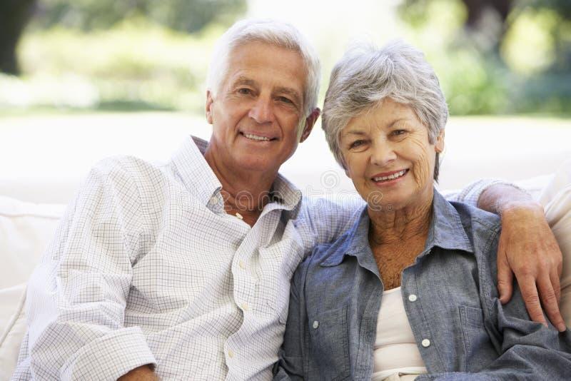 Höga par som hemma kopplar av på sofaen arkivbilder