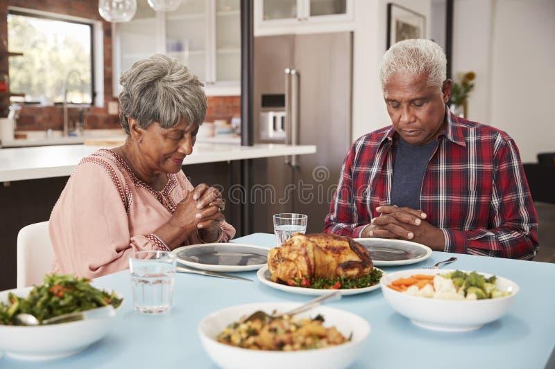 Höga par som hemma säger Grace Before Meal Around Table arkivbild