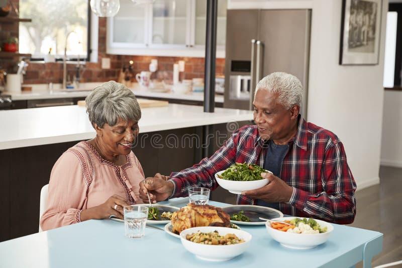 Höga par som hemma tycker om mål runt om tabellen arkivfoton