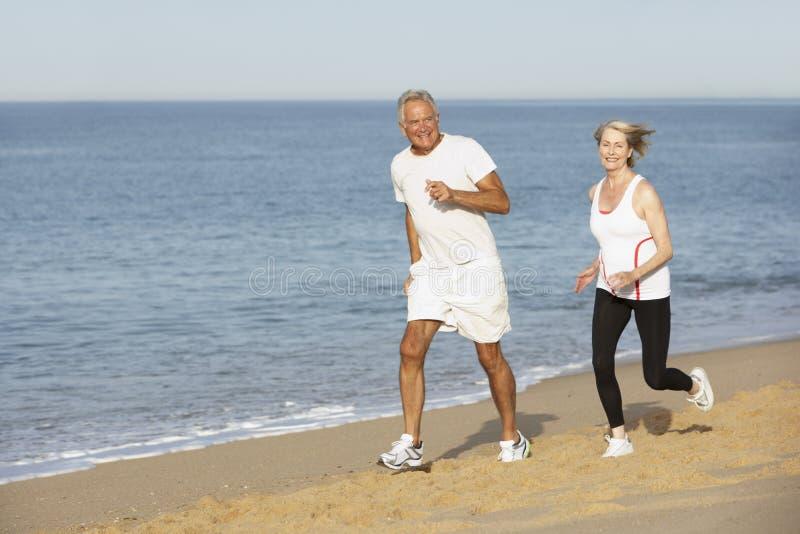 Höga par som joggar längs stranden royaltyfri bild