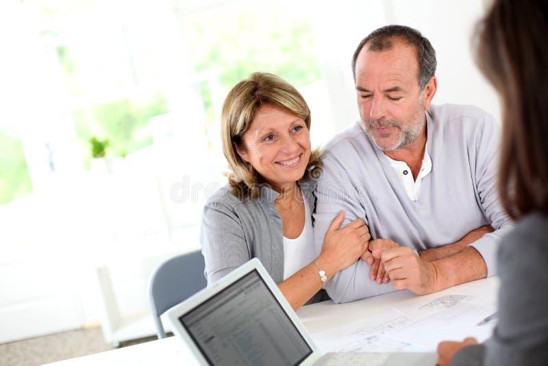 Höga par som köper det nya huset på fastighetbyrån royaltyfria foton