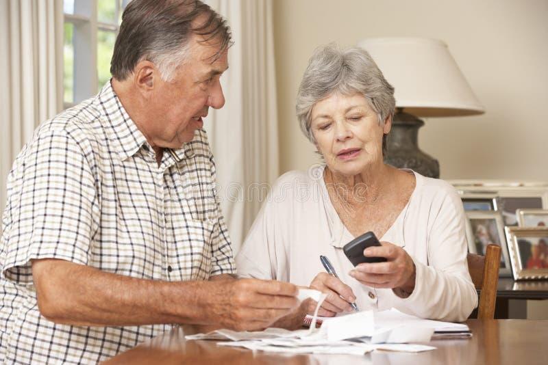 Höga par som kontrollerar finanser och tillsammans går till och med räkningar royaltyfri foto