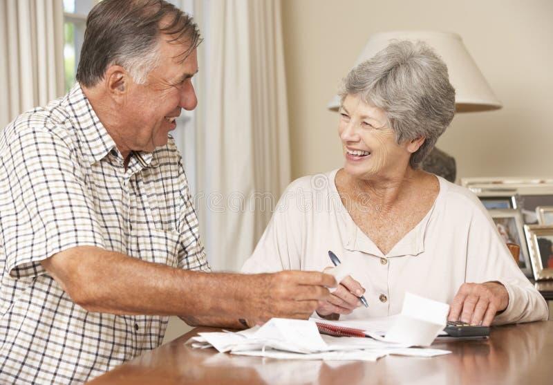 Höga par som kontrollerar finanser och tillsammans går till och med räkningar royaltyfria foton
