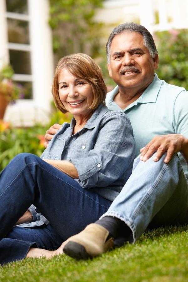 Höga par som kopplar av i trädgård fotografering för bildbyråer