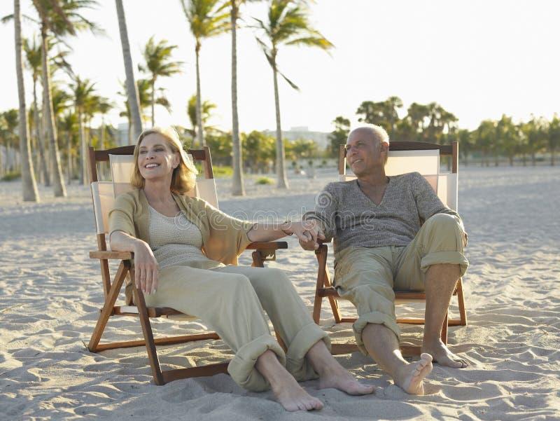 Höga par som kopplar av på Deckchairs på stranden royaltyfria bilder