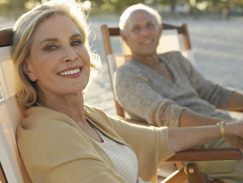 Höga par som kopplar av på den tropiska stranden royaltyfri foto
