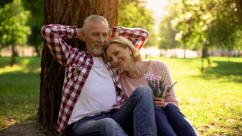 Höga par som kopplar av på gräs parkerar in, och tycker om det romantiska datumet, riktig förälskelse royaltyfria bilder