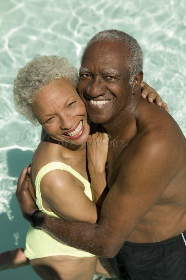 Höga par som kramar i simbassäng arkivfoto