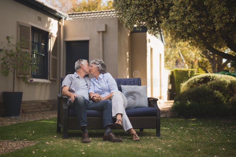 Höga par som kysser, medan sitta i trädgård royaltyfria foton