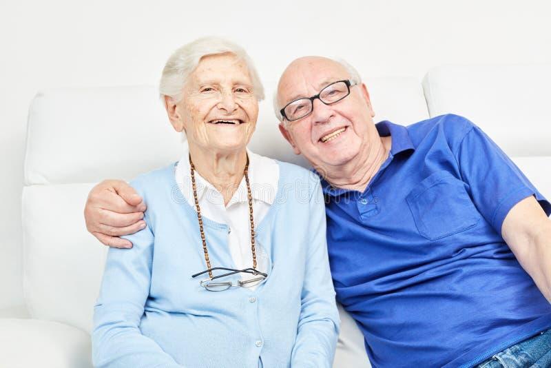Höga par som ler lyckligt på soffan arkivbild