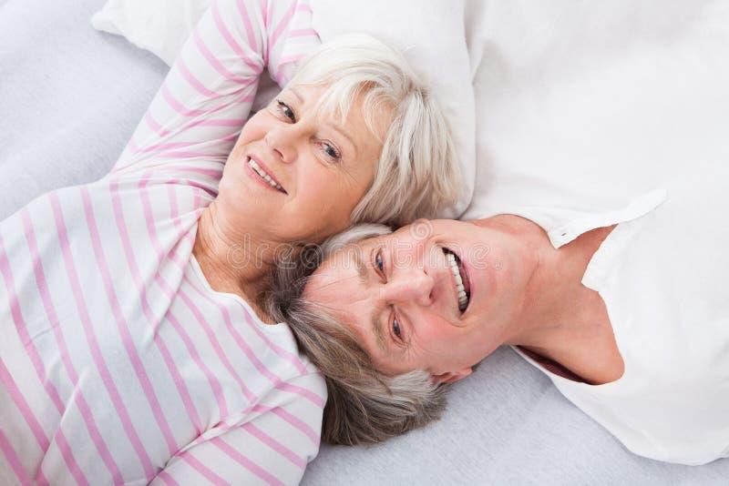 Höga par som ligger på säng royaltyfria foton