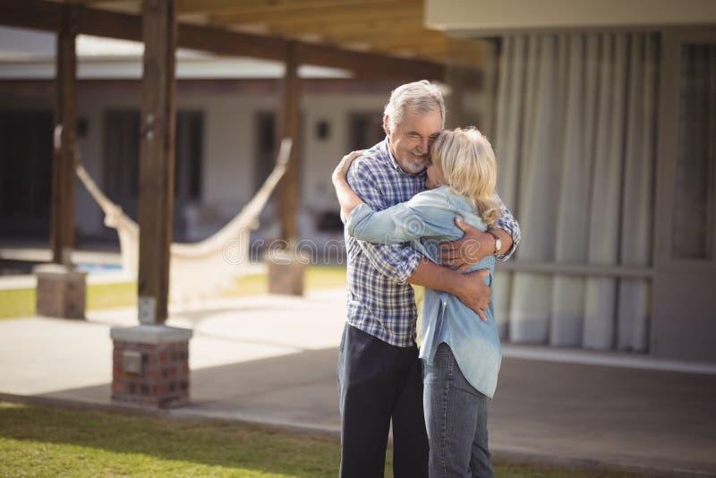 Höga par som omfamnar, medan stå utanför deras hus arkivbild
