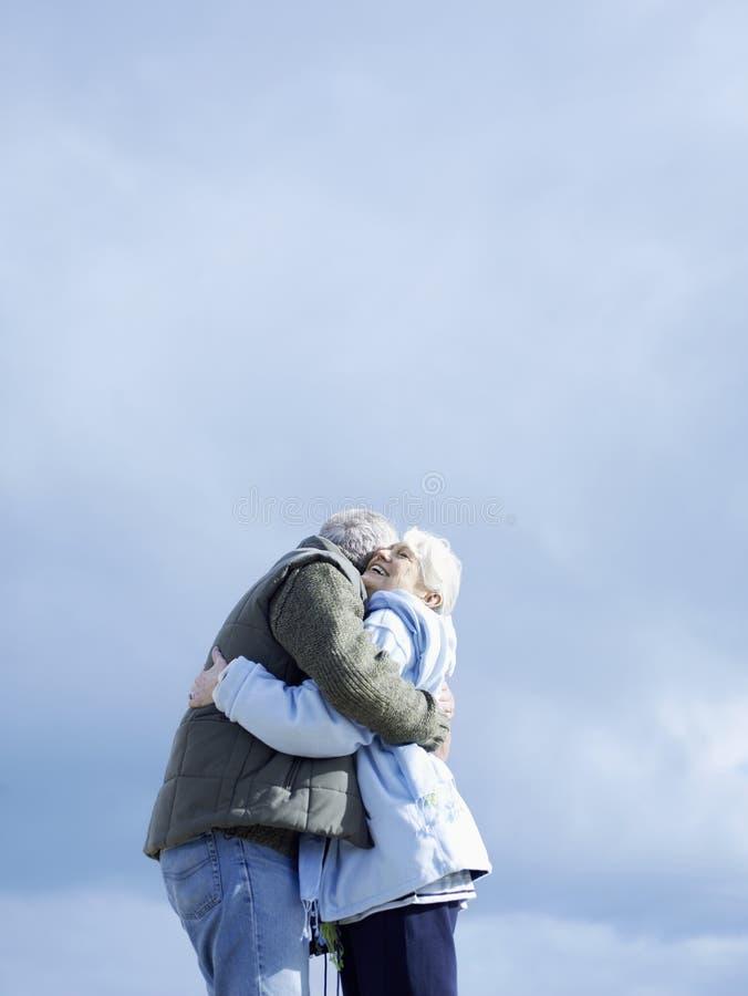 Höga par som omfamnar mot molnig himmel arkivbild